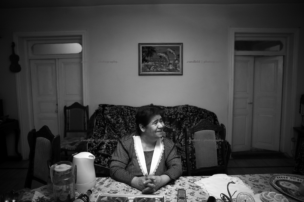 "An armenian Lady sits at a table in her living room. This image is part of the photoproject ""The Twentieth Spring"", a portrait of caucasian town Shushi 20 years after its so called ""Liberation"" by armenian fighters. In its more than two centuries old history Shushi was ruled by different powers like armeniens, persians, russian or aseris. In 1991 a fierce battle for Karabakhs independence from Azerbaijan began. During the breakdown of Sowjet Union armenians didn´t want to stay within the Republic of Azerbaijan anymore. 1992 armenians manage to takeover ""ancient armenian Shushi"" and pushed out remained aseris forces which had operate a rocket base there. Since then Shushi became an ""armenian town"" again. Today, 20 yeras after statement of Karabakhs independence Shushi tries to find it´s opportunities for it´s future. The less populated town is still affected by devastation and ruins by it´s violent history. Life is mostly a daily struggle for the inhabitants to get expenses covered, caused by a lack of jobs and almost no perspective for a sustainable economic development. Shushi depends on donations by diaspora armenians. On the other hand those donations have made it possible to rebuild a cultural centre, recover new asphalt roads and other infrastructure. 20 years after Shushis fall into armenian hands Babies get born and people won´t never be under aseris rule again. The bloody early 1990´s civil war has moved into the trenches of the frontline 20 kilometer away from Shushi where it stuck since 1994. The karabakh conflict is still not solved and could turn to an open war every day. Nonetheless life goes on on the south caucasian rocky tip above mountainious region of Karabakh where Shushi enthrones ever since centuries."