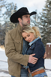 cowboy and a girl embracing while outdoors in the snowy woods of New Mexico