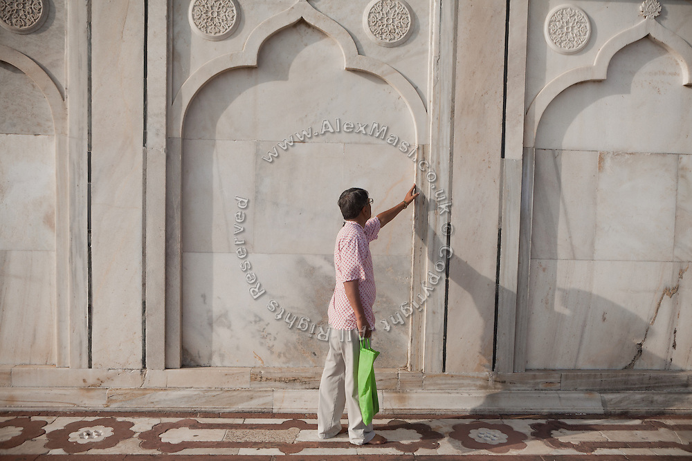 Brij Khandelwal, a renown environmental journalist for the Times of India, is inspecting the damage and conditions of a Markana marble wall inside the Taj Mahal complex.