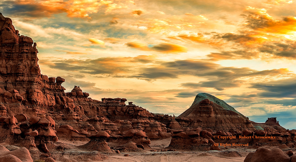 Exposed rock cliffs and hoodoos, with boulders held on high provide a surrealistic setting under an equally unnatural sunset over the Third Valley - Goblin State Park, Utah USA.