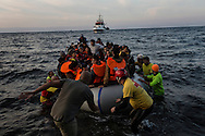 Volunteers guide a boat carrying dozens of asylum seekers to shore after crossing the Aegean from Turkey. Lesvos, Greece, November 7, 2015. <br />