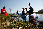 Intro to Marine Science student Sophomore Michael Knowles tries to keep from falling into the marsh as his classmates Freshman Amara Jones (right) Freshman Micah Ducre (center) and Senior JW James (left) search for specific plants to gather for a microcosm kept in a wet lab at Savannah State University, an historically black university in Savannah, Georgia February 9, 2009. KENDRICK BRINSON