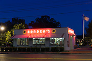 Borden's typical ice cream parlor with Stars and Stripes flag at night in Layfayette,  Louisiana, USA