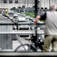Nederland,Leiderdorp ,12 juni 2008... Een half uur lang Langzaamrijdend vrachtverkeer op de autosnelweg A-4, uit protest tegen de stijgende brandstofprijzen en verhoogde accijns op diesel..Traffic jam on one of the main roads of The Netherlands.