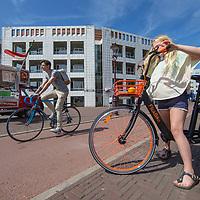 Nederland, Amsterdam, 9 juli 2017.<br /> De Amsterdamse start-up FlickBike test deze zomer een naar eigen zeggen &lsquo;vernieuwend deelfietsconcept&rsquo;. Het experiment omvat duizend fietsen, die realtime te vinden zijn via een gratis app. Gebruikers downloaden de app, zoeken een fiets in de buurt en openen het fietsslot met hun telefoon.<br /> <br /> Anders dan bij veel bestaande deelfietsconcepten, laten fietsers een FlickBike gewoon achter op hun bestemming. Teruggaan naar een huurstalling of fietsverhuurstation is niet meer nodig.<br /> Op de foto: Meisje zet Flick bike op slot.<br /> <br /> <br /> Foto: Jean-Pierre Jans