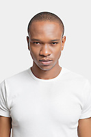 Portrait of serious young man in white t-shirt against white background