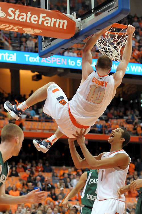 Syracuse Orange guard TREVOR COONEY (10) hangs on the rim as teammate Syracuse Orange guard MICHAEL CARTER-WILLIAMS (1) comes to help him down after the dunk and the foul against the Eastern Michigan Eagles during the second half at the Carrier Dome in Syracuse, New York. Number four ranked Syracuse defeated Eastern Michigan 84-48 in front of a crowd of 20,822.