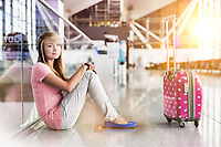 Portrait of young teenage girl sitting on the floor in airport