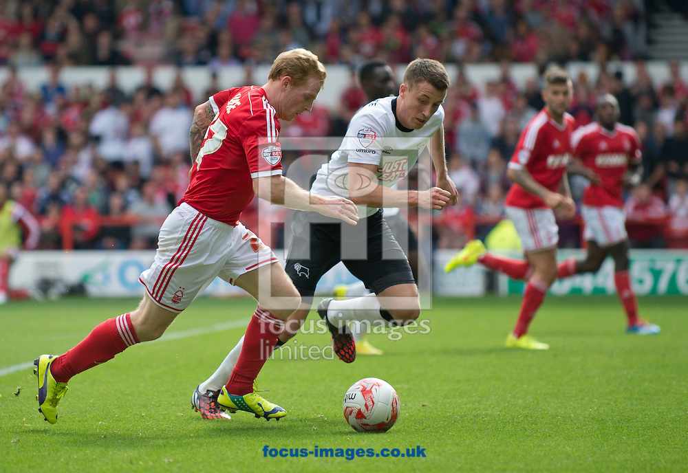 Chris Burke of Nottingham Forest attempts to out-pace Craig Forsyth of Derby County during the Sky Bet Championship match at the City Ground, Nottingham<br /> Picture by Russell Hart/Focus Images Ltd 07791 688 420<br /> 14/09/2014