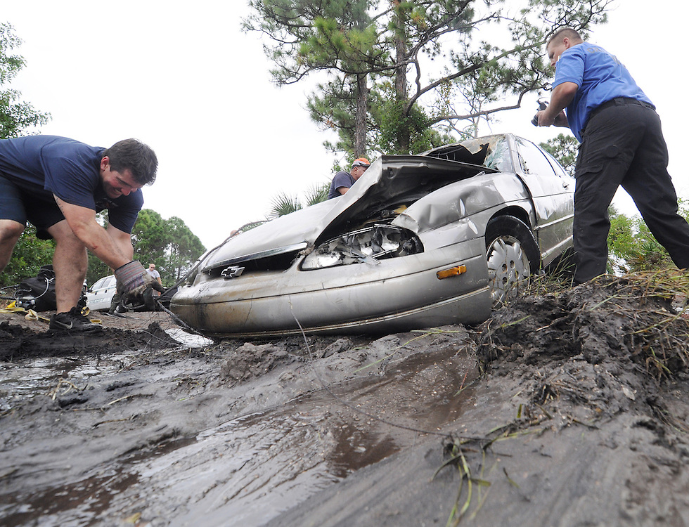 "Andrew Knapp, FLORIDA TODAY -- Oct. 19, 2011 -- Melbourne crime-scene investigators photograph a Monte Carlo that was pulled from a remote pond southwest of Wuesthoff Medical Center-Melbourne on Wednesday, part of ""Operation Muddy Wheels."" The effort removed six vehicles that were dumped in the pond; most were stolen."