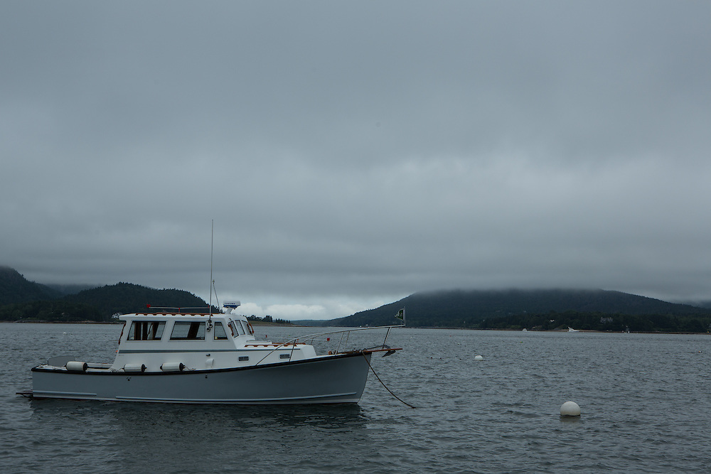 Southwest Harbor, ME - 13 August 2014. Motorboat Dasbote at a mooring of Clarks Point, looking up to the entrance to Somes Sound in the fog.