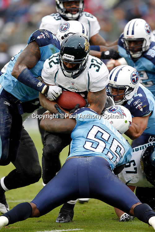 Jacksonville Jaguars running back Maurice Jones-Drew (32) gets gang tackled by Tennessee Titans linebacker Stephen Tulloch (55), Tennessee Titans safety Chris Hope (24), and an unidentified player during the NFL week 13 football game against the Tennessee Titans on Sunday, December 5, 2010 in Nashville, Tennessee. The Jaguars won the game 17-6. (©Paul Anthony Spinelli)