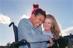 Care manager and young woman with Cerebral Palsy laughing together in park,