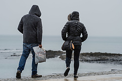© London News Pictures. 07/05/2016. Aberystwyth, UK. People on  the damp promenade in Aberystwyth. As much of England swelters on the hottest day of the year so far, much of the west and Wales is experiencing a wet and rainy day. A Met Office amber warning is in place for the whole of Wales for the rest of the day, with the possibility of torrential localised downpours. Photo credit: Keith Morris/LNP