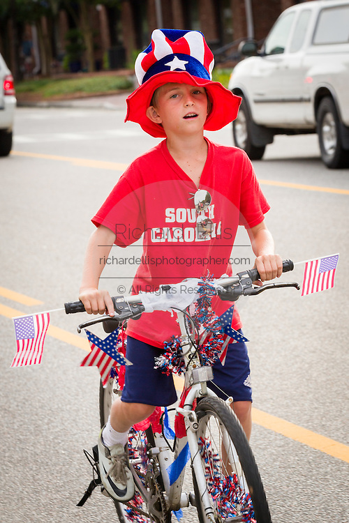 A young boy rides his bicycle decorated with bunting during the Daniel Island Independence Day parade July 3, 2015 in Charleston, South Carolina.