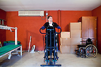 29 December, 2009. Bronxville, NY. Francesco Clark, 30, founder and president of Clark's Botanicals, exercises on the standing frame (or easy stand) in the garage of his home office in Bronxville. Francesco Clark suffers a crippling cord injury due to a swimming pool diving accident on June 1, 2002. Clark's Botanicals was born out of the tragedy.<br /> With his central nervous system impaired, Francesco, who was then an assistant stylist at Harper's Bazar, lost the ability not only to walk, but even to sweat. This led to clogged pores and chronic breakouts. When neither over-the-counter nor prescriptive remedies worked, he turned to his father, Dr. Harold Clark, a physician trained in both traditional Western medicine and homeopathy.<br /> <br /> Together they developed botanically-based formulas that effectively rebalanced Francesco's skin, clearing it up entirely. Through word-of-mouth, other people discovered and fell in love with these products, and in 2005, Francesco began selling Clark's Botanicals on his website.<br /> ©2009 Gianni Cipriano for The New York Times<br /> cell. +1 646 465 2168 (USA)<br /> cell. +1 328 567 7923 (Italy)<br /> gianni@giannicipriano.com<br /> www.giannicipriano.com