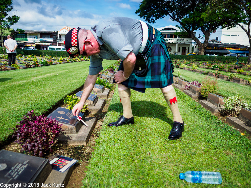 """11 NOVEMBER 2018 - KANCHANABURI, KANCHANABURI, THAILAND: STEWART WILSON, a Scottish veteran of the British army, leaves a cross on the grave of a Scottish soldier killed on the """"Death Railway"""" during the Rememberance Day ceremony at the Kanchanaburi War Cemetery in Kanchanaburi, Thailand. Kanchanaburi is the location of the infamous """"Bridge On the River Kwai"""" and was known for the """"Death Railway"""" built by Japan during World War II using allied, principally British, Australian and Dutch, prisoners of war as slave labor. There are 6,982 people buried in the cemetery, including 5,000 Commonwealth soldiers and 1,800 Dutch soldiers. November 11, 2018 marked the 100th anniversary of the end of World War I, celebrated as Rememberance Day in the UK and the Commonwealth and Veterans' Day in the US.     PHOTO BY JACK KURTZ"""