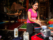 """12 FEBRUARY 2019 - SIHANOUKVILLE, CAMBODIA:  The wife of a Cambodian construction worker (in hammock in the background) makes dinner in their home in the Blue Bay casino and resort, a Chinese project in Sihanoukville. There are about 50 Chinese casinos and resort hotels either open or under construction in Sihanoukville. The casinos are changing the city, once a sleepy port on Southeast Asia's """"backpacker trail"""" into a booming city. The change is coming with a cost though. Many Cambodian residents of Sihanoukville  have lost their homes to make way for the casinos and the jobs are going to Chinese workers, brought in to build casinos and work in the casinos.     PHOTO BY JACK KURTZ"""