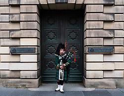 Scottish piper playing bagpipes on Royal Mile outside Edinburgh High Court in Edinburgh Old Town, Scotland ,UK