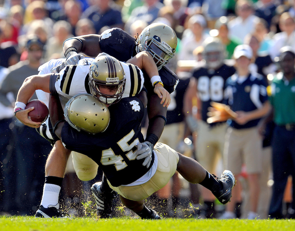 Linebacker Darius Fleming (45) and defensive end Hafis Williams (94) bring down Western Michigan Broncos quarterback Alex Carder (14).