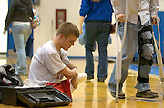 2006.02.02 HILLSBOROWRESTLER SPORTS : Hillsboro sophomore wrestler Dustin Carter tapes his legs as he preapares for his match Thursday February 2, 2006. Dustin said he needs to tape his legs for protection. The skin can be very sensitive. The Enquirer/Jeff Swinger