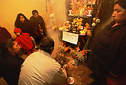 A family calls down the spirit of a dead family member with the help of incense at Todos Santos or All Saints Day in Oruro, Bolivia. An altar has been built at home, and it is the father of the dead man who kneels with the incense in front of it. Beside him kneels the widow, and to the right stands the mother. In the Altiplano of Bolivia, it is customary that a family, in which there has been a death within the last three years, build a shrine at home at Todos Santos, decorating it with religious symbols as well as a picture of the deceased and food and drink that he or she liked, and then call down the spirit for a three day visit. During the spirit's visit, the family and friends chew coca leaves, drink alcohol and eat food together.