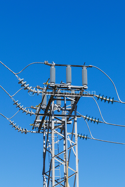 High voltage three phase electricity power lines and insulators on a metal tower in a urban substation