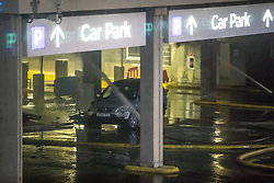 © Licensed to London News Pictures . 01/01/2018. Liverpool, UK. Fire hoses spray water in the entrance to the car park which runs underneath an apartment block . Scene at the Liverpool Echo Arena car park where firefighters are working to extinguish a fire that started late on New Year's Eve and that destroyed all 1,400 cars parked in the multi-story car park. The Liverpool International Horse Show taking place at the Arena was abandoned and people and horses evacuated as dozens of fire crew worked to control the blaze . Photo credit: Joel Goodman/LNP