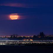 """A rare """"super moon"""" shining through the clouds above a dairy farm - Chandler, AZ"""