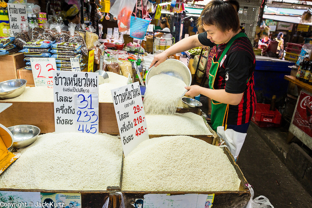 """24 AUGUST 2013 - BANGKOK, THAILAND:     A rice seller sets up his market stall in Khlong Toei Market in Bangkok. Thailand entered a """"technical"""" recession this month after the economy shrank by 0.3% in the second quarter of the year. The 0.3% contraction in gross domestic product between April and June followed a previous fall of 1.7% during the first quarter of 2013. The contraction is being blamed on a drop in demand for exports, a drop in domestic demand and a loss of consumer confidence. At the same time, the value of the Thai Baht against the US Dollar has dropped significantly, from a high of about 28Baht to $1 in April to 32THB to 1USD in August.    PHOTO BY JACK KURTZ"""