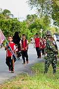 """Sept. 27, 2009 -- PATTANI, THAILAND: Thai soldiers provide security for children walking to the Gahong School in Pattani, Thailand, Sept 27. Schools and school teachers have been frequent targets of Muslim insurgents in southern Thailand and the army now provides security at many government schools.  Thailand's three southern most provinces; Yala, Pattani and Narathiwat are often called """"restive"""" and a decades long Muslim insurgency has gained traction recently. Nearly 4,000 people have been killed since 2004. The three southern provinces are under emergency control and there are more than 60,000 Thai military, police and paramilitary militia forces trying to keep the peace battling insurgents who favor car bombs and assassination.  Photo by Jack Kurtz"""