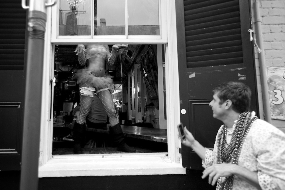 A man stops to take a picture of an erotic dancer at a bar window on Bourbon Street during Mardi Gras in New Orleans, LA. Kris Ugarriza - Red Wave Pictures