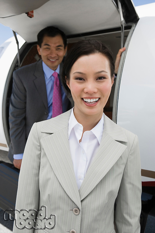 Portrait of mid-adult businesswoman standing in front private jet, colleague behind.
