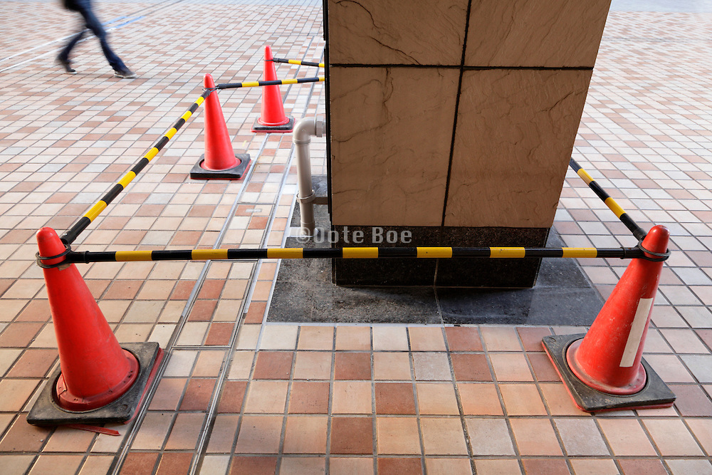 safety cones with bars surrounding a pillar