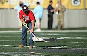A grounds crew shovels pellets as he works at mid-field trying to remove a painted logo that caused footing problems with player cleats before the Green Bay Packers 2016 NFL Pro Football Hall of Fame preseason football game against the Indianapolis Colts on Sunday, Aug. 7, 2016 in Canton, Ohio. The game was canceled for player safety reasons due to the condition of the paint on the turf field. (©Paul Anthony Spinelli)