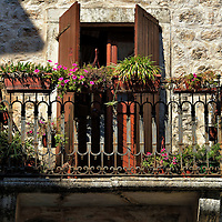 Flowerboxes on Balcony Railing in Kotor, Montenegro<br /> Kotor is built from stone … stone walls, facades and streets. I don't recall seeing a single blade of grass in the town. So it was refreshing to see how one resident decorated their ornamental iron railing with flowerboxes.  What a perfect spot for this tiny touch of nature! Notice how the afternoon sun perfectly conforms to the balcony.