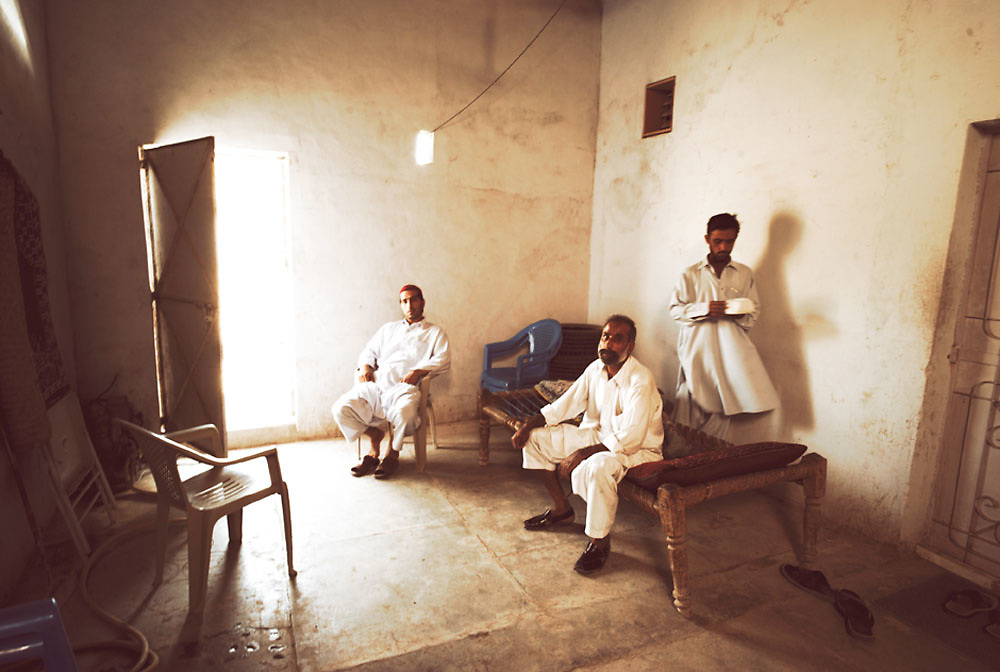Men wait inside a room for a delivery of heroine to arrive from a courier at the Smuggler's Bazaar, Khyber-Pakhtunkhwa, Pakistan on 25th Sep, 2007...
