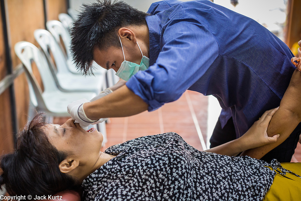 05 MARCH 2014 - MAE SOT, TAK, THAILAND: A medic pulls a patient's tooth in the dental clinic at the Mae Tao Clinic in Mae Sot. The Mae Tao Clinic provides  healthcare to over 150,000 displaced Burmese per year and is the leading healthcare provider for Burmese along the Thai-Myanmar border. Reforms in Myanmar have alllowed NGOs to operate in Myanmar, as a result many NGOs are shifting resources to operations to Myanmar, leaving Burmese migrants and refugees in Thailand vulnerable.     PHOTO BY JACK KURTZ
