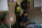 Tabasum Khatun, 14, is studying the Holy Koran inside her home in Algunda village, pop. 1000, Giridih District, rural Jharkhand, India.