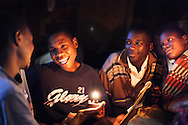 Four brothers, Lawrence (15), Geoffrey (14), Joseph (15) and Deo (12) enjoy a joke over shared school homework before bedtime. The boys, orphaned by AIDS, take it in turns (two at a time) to go to school whilst the other two look for casual work in order to support themselves.<br /> <br /> Rural area near Jinja, Uganda