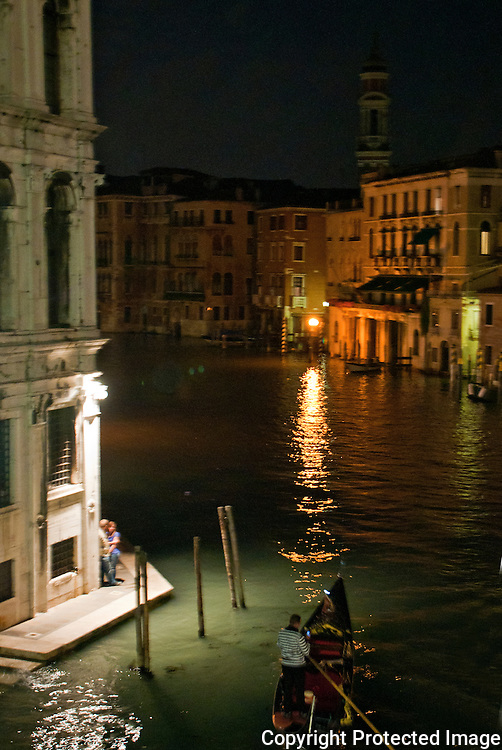 Romantic couple and a gondola seen from the Rialto Bridge on the Grand Canal at night in Venice, Italy.