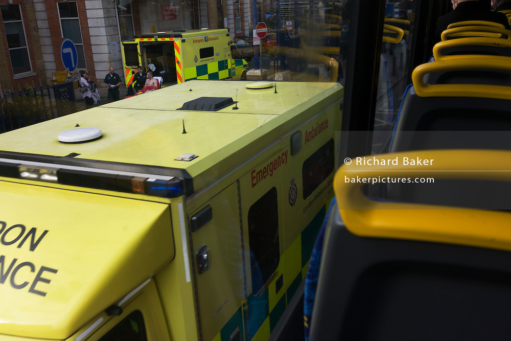 Seen from the top deck of a London bus, a hospital casualty arrives by ambulance outside A+E.
