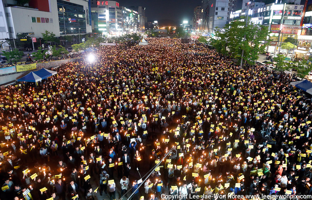 Participants hold candles during a rally against what they insist, lax response of President Park Geun-hye's government after the Sewol ferry was sunken in waters off the southwestern island of Jindo on April 16, 2014, at a plaza in Ansan, south of Seoul, May 10, 2014. About 13,000 people participated in the rally to ask for resignation of President Park and to mourn for victims of the tragedy, according to local media. Photo by Lee Jae-Won (SOUTH KOREA) www.leejaewonpix.com/