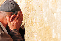 A Jewish man leans into the Western Wall and prays, his face in his hands. The Western Wall is the holiest site in Judaism. (Jerusalem - October 20, 2010)