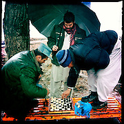 A policeman plays chess in Shar-e Now Park.