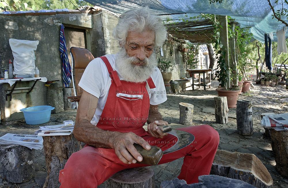 Castelbuono, Giulio Gelardi, sharpens the special sickle used to make etchings in the trees.<br /> <br /> Castelbuono, Giulio Gelardi, affila la speciale falce usata per intaccare gli alberi.