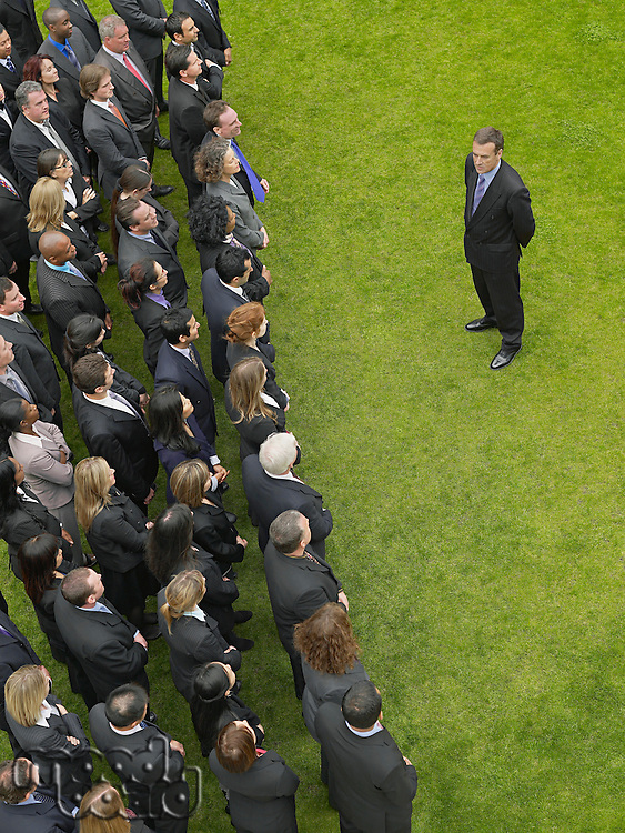 Business man facing large group of business people in formation elevated view