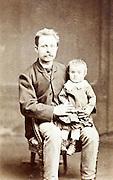 vintage studio portrait father with little child sitting