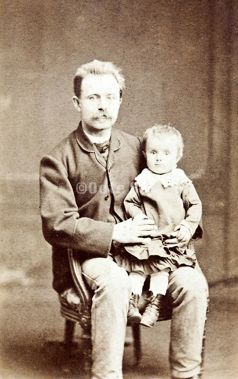 vintage studio portrait father with little child sitting