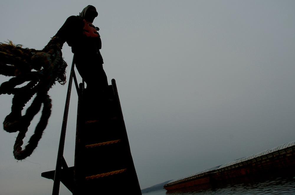 Illinois River towboat deckhand Bill Beard works on misty early morning. ©David Zalaznik